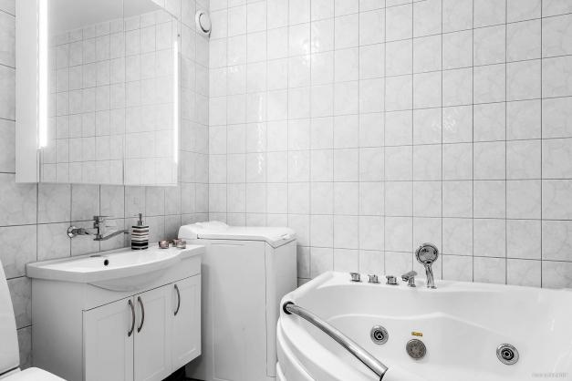 Helkaklat badrum med hörnbubbelbadkar med belysning