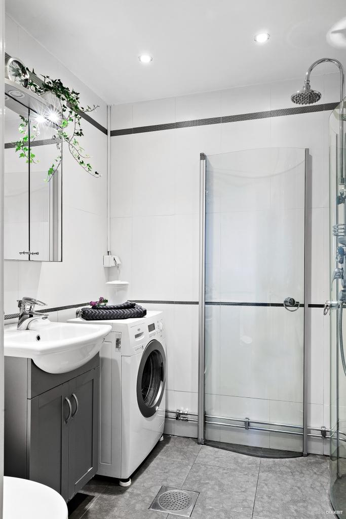 Stilrent badrum med spotlights och tvättmaskin.