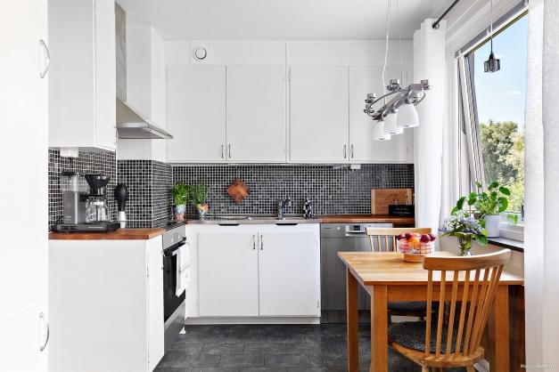Snyggt kök med ljusa luckor och rostfria vitvaror. Bordet har sin givna plats vid fönstret.