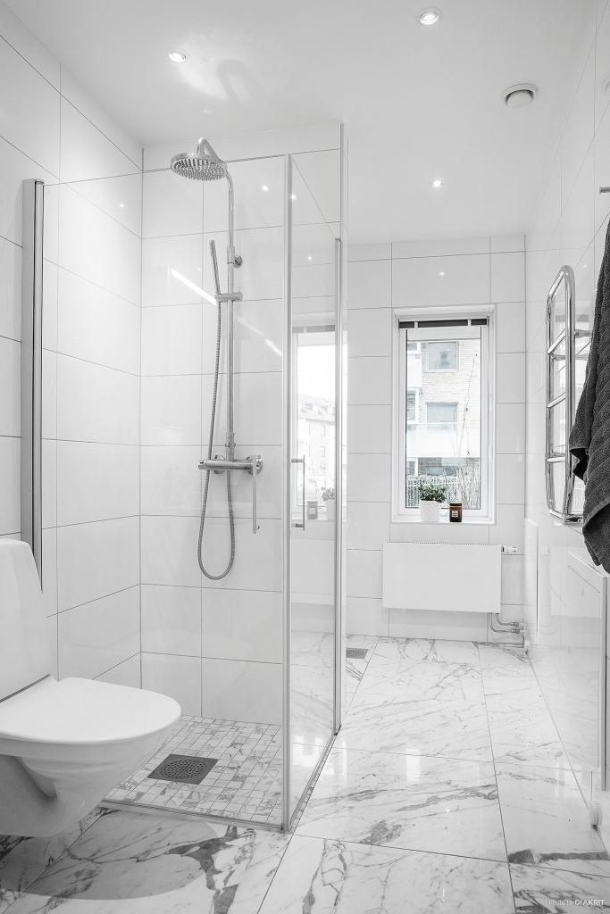 Helkaklat vitt badrum med dusch från Svedbergs.