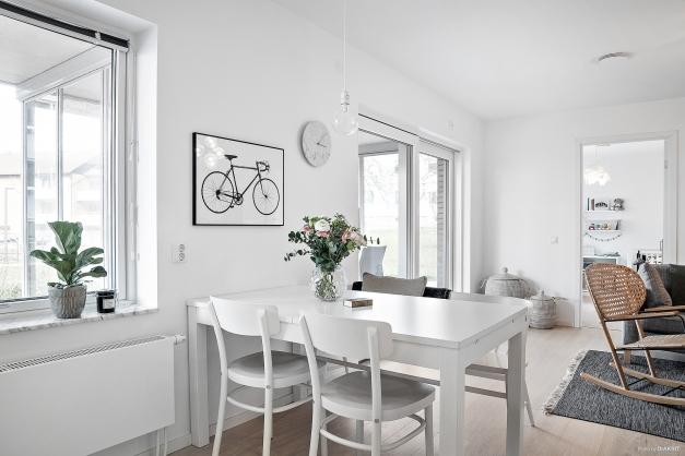 Genomtänkt planlösning mellan kök och vardagsrum med utrymme för matplats.