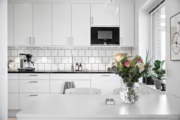 Vit modern köksinredning med släta luckor från Marbodal och bänkskiva i svart natursten.