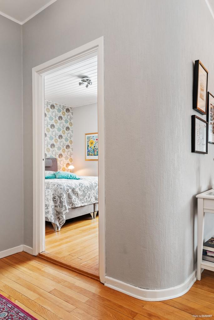 """Hall med titt in i sovrummet. Det """"runda hörnet"""" ger lägenheten en riktigt skön karaktär!"""