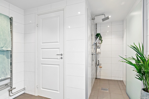 Generös dusch innanför glasdörrar