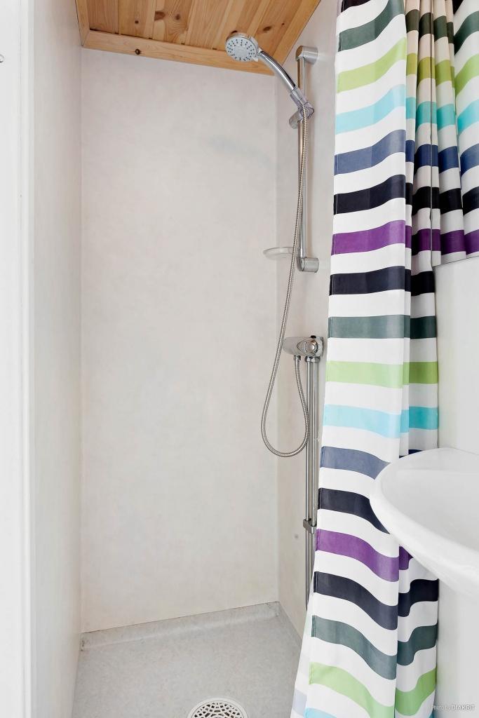 Vid hallen finns ett duschrum med wc-stol och tvättmaskin.