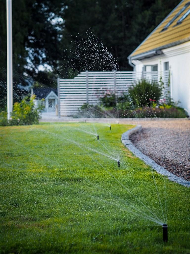 Sprinklersystem i gräsmattan om sommaren (säljarens egen bild)