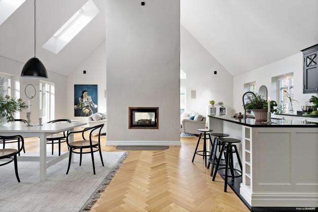 Umderbart vardagsrum med öppet till nock. En fantastisk murstock blir centrum i rummet med tunnelkassett