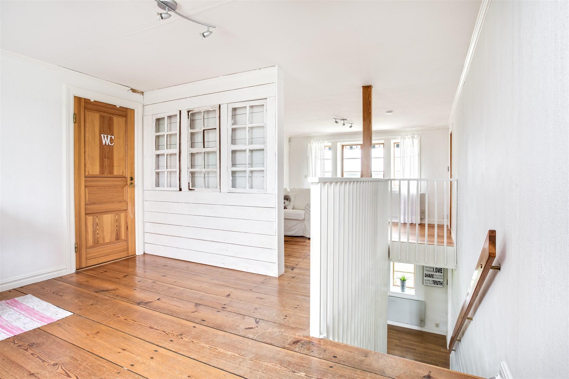 Allrummet har en avskiljande vägg med gamla fönster mot ena sidan.