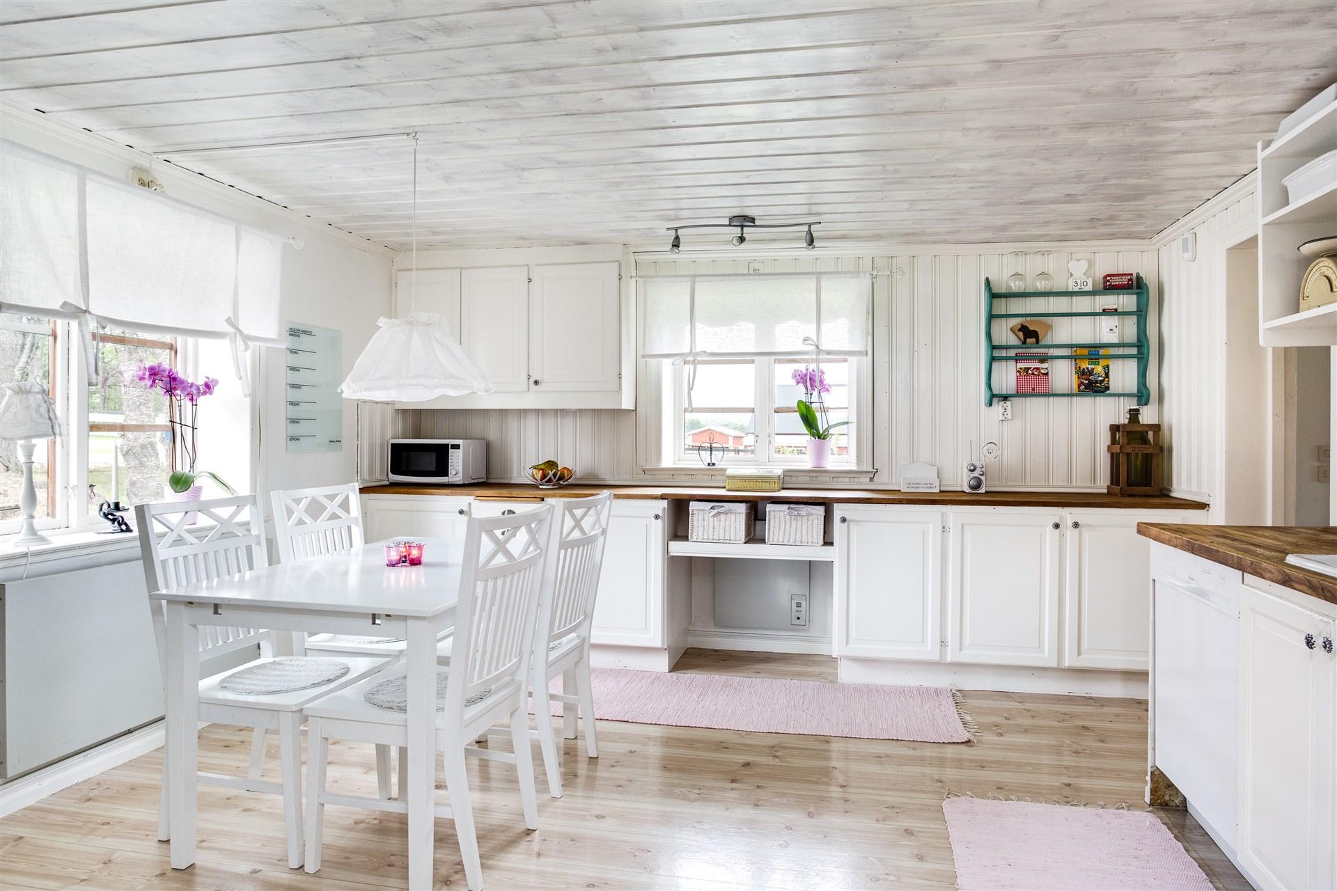 Köket har delvis vit panel på vägg och bänkskivor i ek.