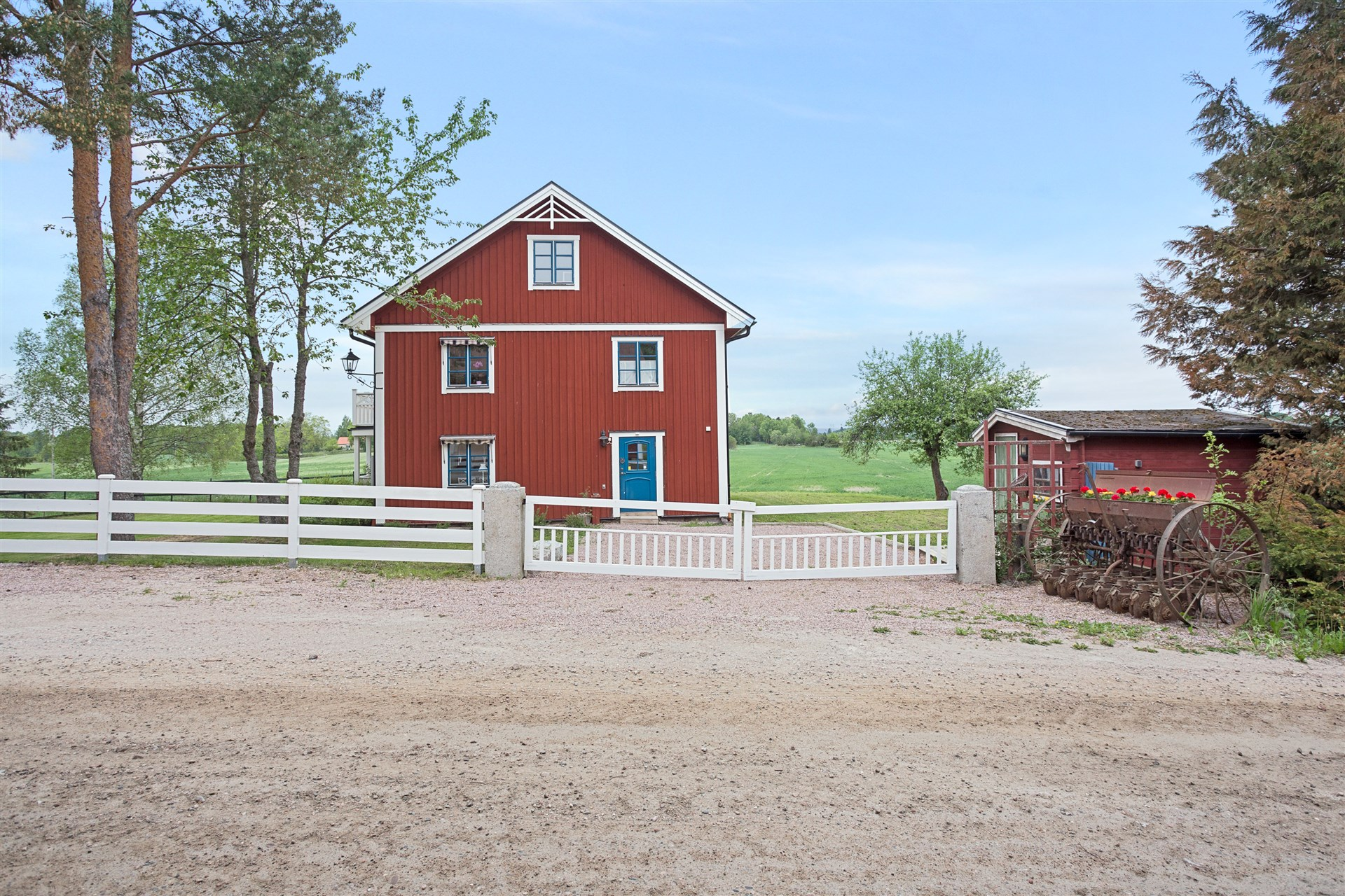 Infart till huset med fint staket och grindar.