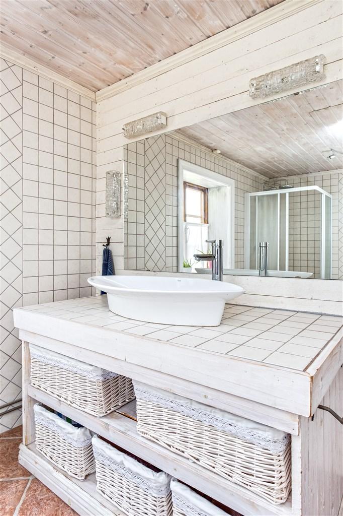 Dusch/wc med kakel på vägg och klinker på golv med golvvärme.
