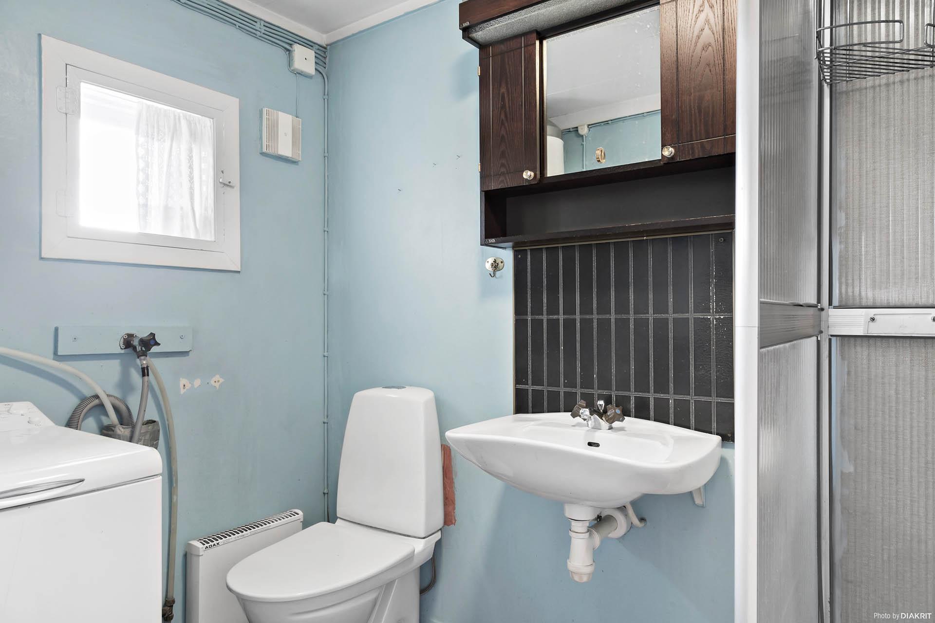 Badrum med tvättmaskin, wc, handfat, spegelskåp och dusch.