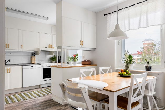 Ljust trivsamt kök med matplats framför fönstret