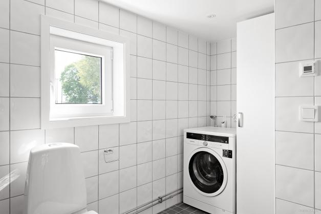 Helkaklat duschrum med tvättmaskin.