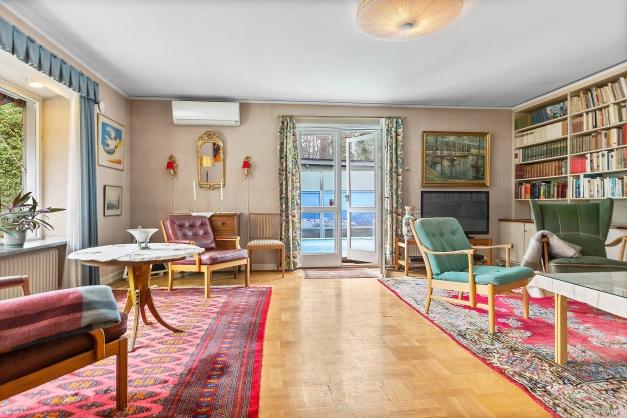 Ljus, rymligt vardagsrum med vakert golv och platsbyggd bokhylla.