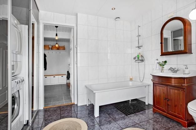 Praktisk och funktionell tvättdel bakom spegelskjutdörrar.