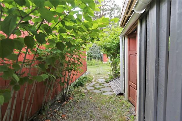 Gång ned till tomten mellan hus och garage.