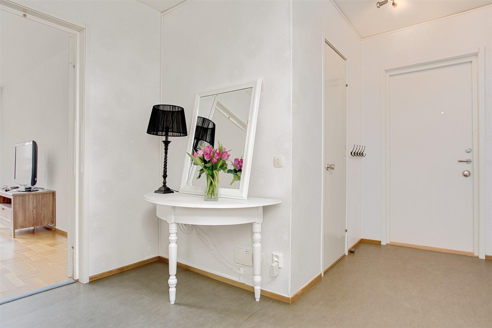 Ljus hall med klädkammare och plats för mindre möblemang.