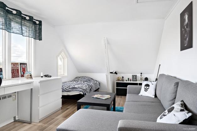 Sovrum/kontor med laminatgolv och snedtak.
