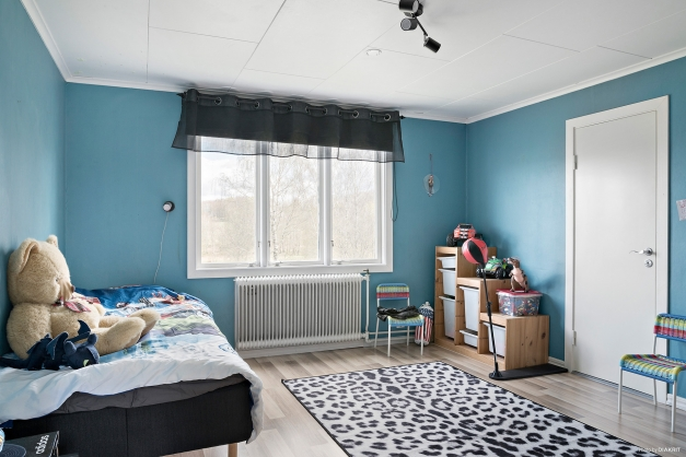 Sovrum i behagliga färger med laminatgolv.