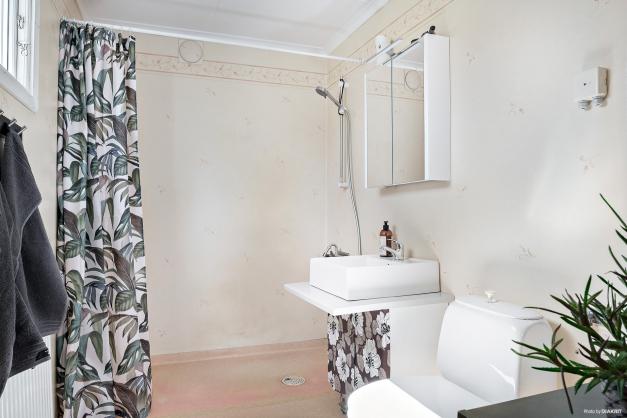 Badrum med dusch, tvättställ och WC. Plastmatta på golvet och våtrumstapet.