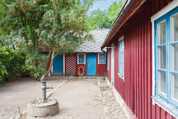 Välkommen till ett charmigt rödmålat hus med vita knutar.