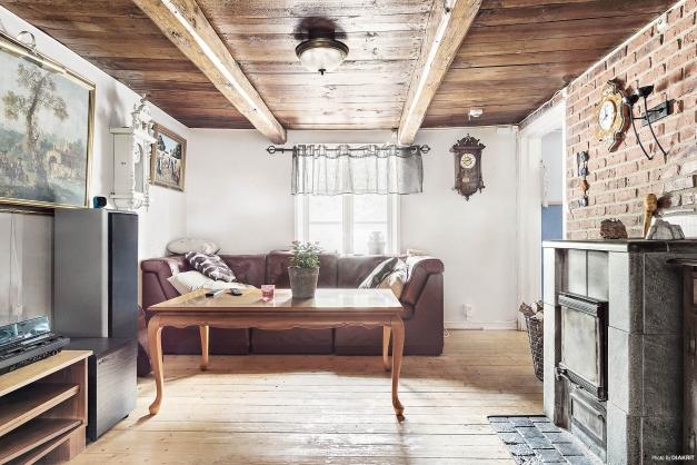 Tegelvägg i vardagsrummet, resterande väggar är målade lerstensväggar. Här finns även en trivsam kamin i täljsten. som värmer skönt under den svalare årstiden.