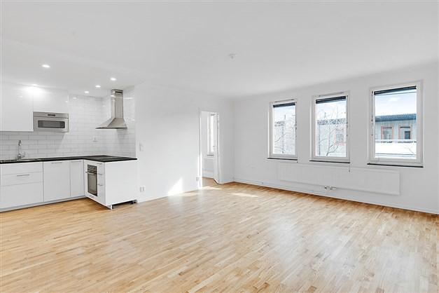 Vardagsrum och kök i ljus och öppen planlösning.