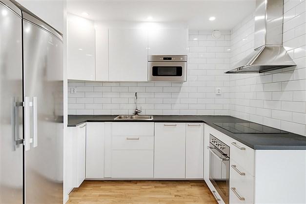 Kök med rostfria vitvaror, vita skåpsluckor, laminatbänkskiva, vitt kakel på vägg.
