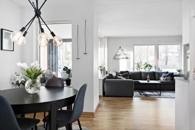 Vardagsrum med öppen planlösning mot kök och matplats och ljusinsläpp från två håll.