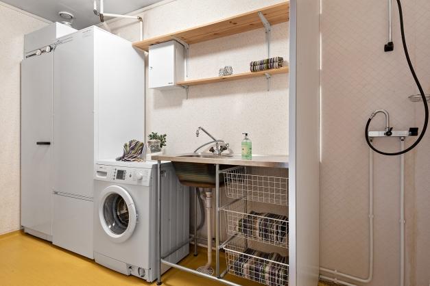 Tvättstuga med tvättmaskin, torkskåp och duschplats. Här finns även husets varmvattenberedare
