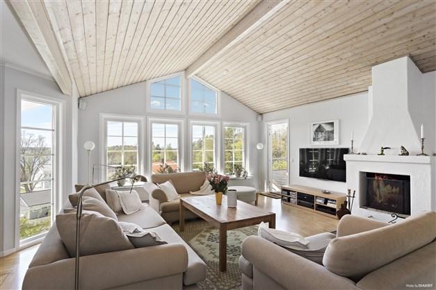 Vardagsrummet med murad spis och dörr mot trädäck