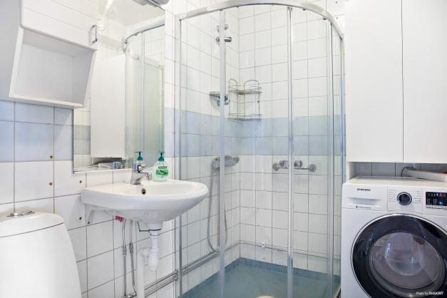 Badrum med dusch och tvättmaskin.