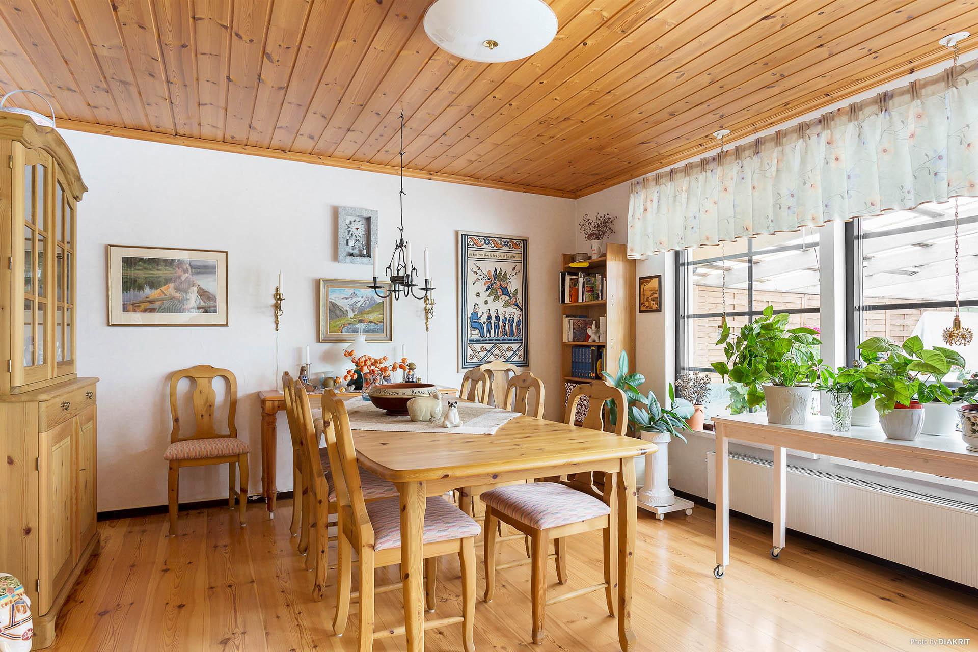 Stora fönsterpartier i vardagsrum med vy över altan och hästhagar