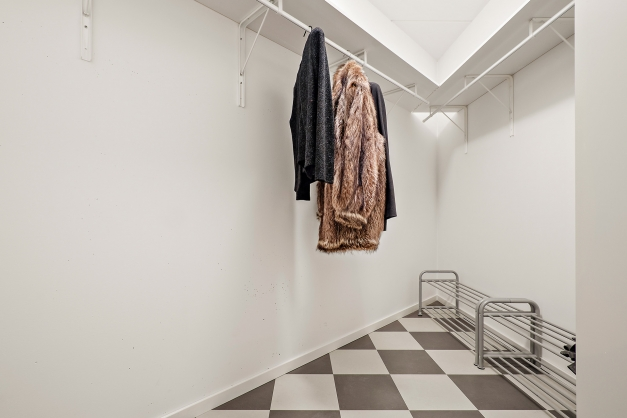 Walk in closet i anslutning till hallen med nylagt klickgolv.