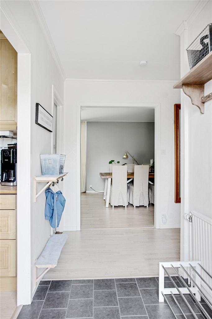 Ljusa trägolv i hall, kök och vardagsrum.