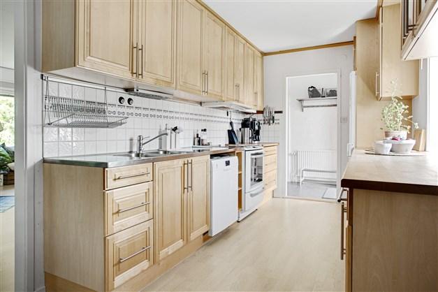 Ljust kök med träfärgade luckor.