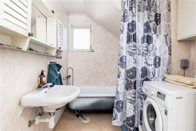 Badrum med wc, handfat, badkar och tvättmaskin