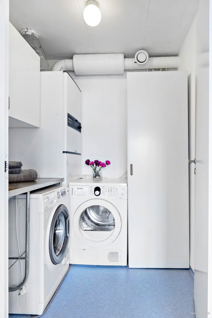 Tvättstuga med tvättmaskin och torktumlare, båda från 2014.