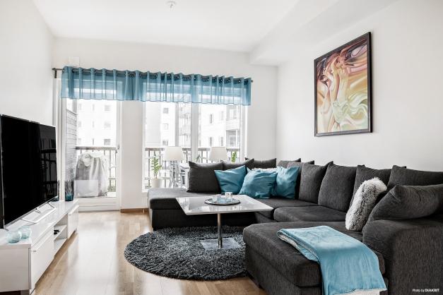 Stort vardagsrum med härlig takhöjd och utanför väntar en av lägenhetens generösa balkonger