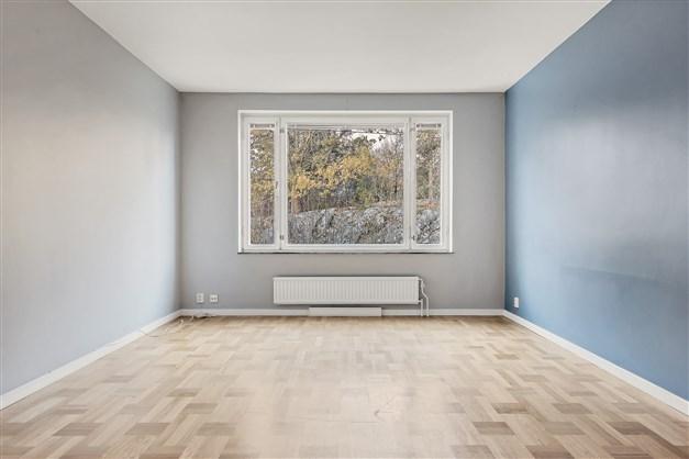 Vardagsrum med blå väggar och vacker originalparkett
