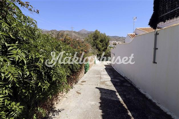 Privat väg med grindar sista biten fram till tomten. Vägen delas med 2 grannar.
