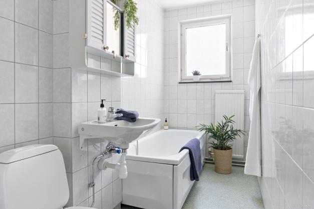 Det större badrummet med badkar och tvättmaskin