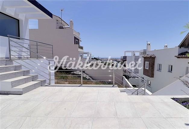 Stilren terrass med plats för solstolar och sittgrupp