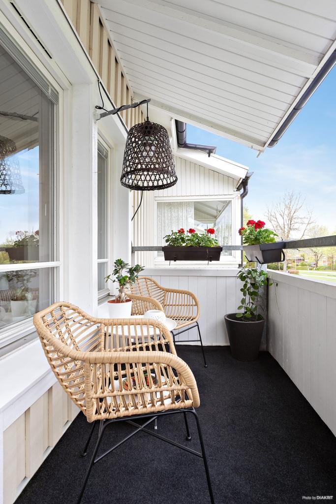 Trevligt balkong med matta på golv blir på sommaren en förlängning av vardagsrummet