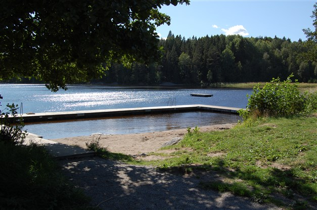 Stora gräsytor kring badet och en liten strand.