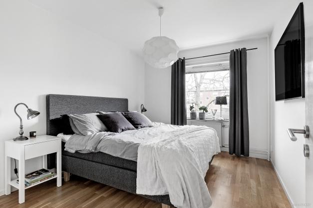 Sovrum med ljusa väggar och plats för dubbelsäng.