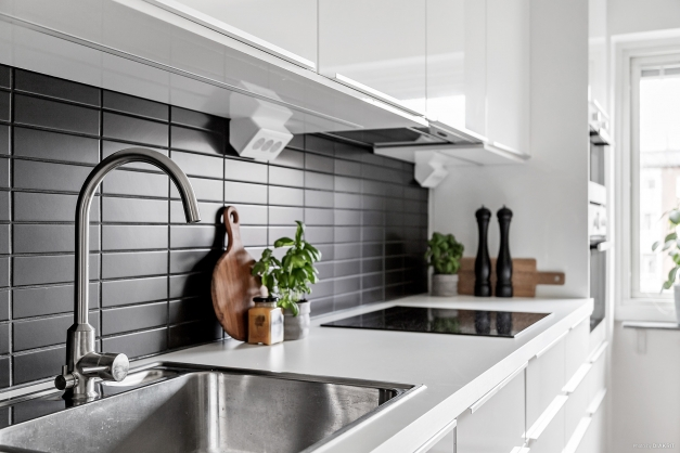 Vita skåpsluckor och svart kakel i köket.