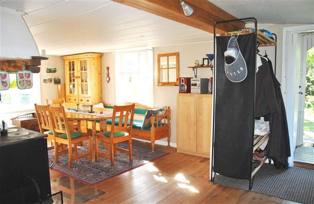 Öppen planlösning mellan kök och matplats med vedspisen som en central punkt