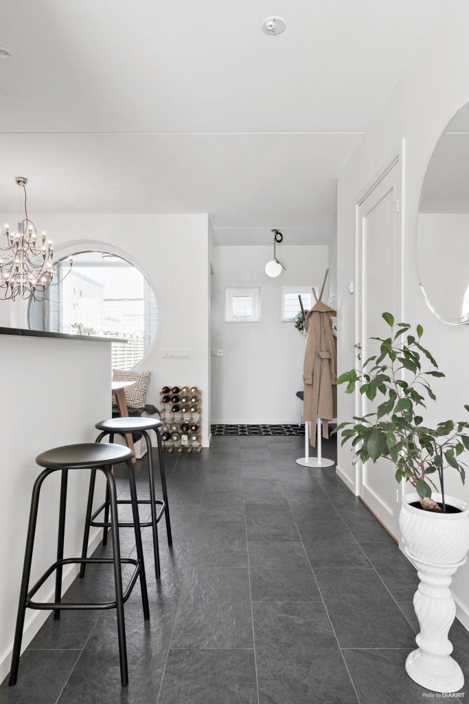 Hallen. Här ligger ett tåligt klinkergolv i mörkt grå ton. Ljust målade ytor i övrigt. Hela huset har vattenburen golvvärme.